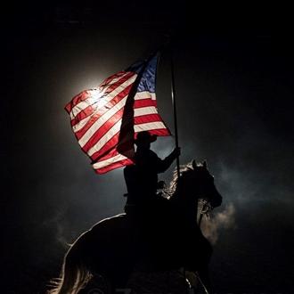Photograph of cowboy on horseback holding the USA Flag