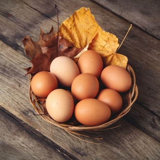 Photo: Basket of brown, chicken eggs with a yellow autumn leaf tucked in the eggs