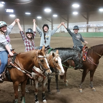 Philomath Equestrian Team members on horse back, holding hands raised in victory