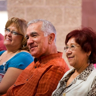 Photograph of smiling adults listening to a presentation