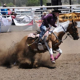 Photograph of cowgirl on her horse barrel racing