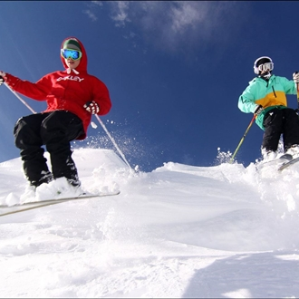 Photograph of two skiers on a snowy slope with a bright blue sky in the background