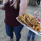 Photo: woman holding a large plate of curly fries with a young boy, wide-eyed, mouth open in amazement!