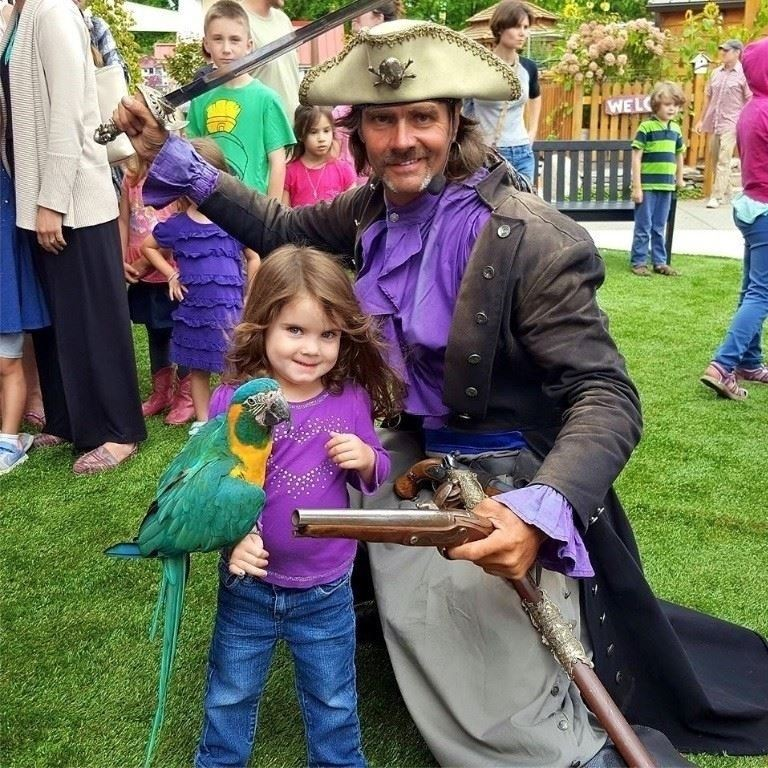 Photo: Young girl posing with parrot and bird handler dressed as a pirate