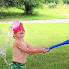 Blind folded child swing a plastic bat at a water balloon 'pinata'