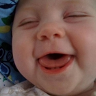 baby with open mouthed smile and closed eyes