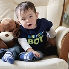 Toddler in a chair with  a stuffed dog toy