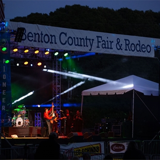 Night view of Benton County Fair & Rodeo concert stage with a performer on stage