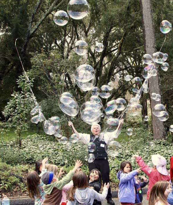 Photo: an outdoor scene filled with children reaching for bubles created by performer