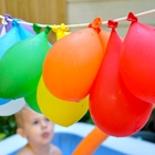 Young boy looking up at water balloons  hanging on a line