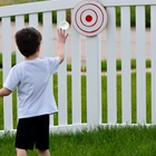 Young boy throwing a water balloon at a target