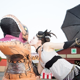 Photo: Stiltwalker Radiance kissing  man in a T-Rex dinosaur costume