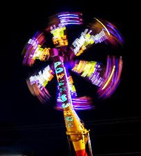 Photo: Night shot of carnival ride spinning high up in the air.