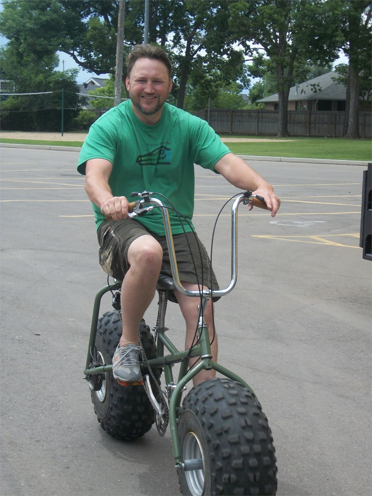 Man on a green bike with huge tires in south midway of fairgrounds