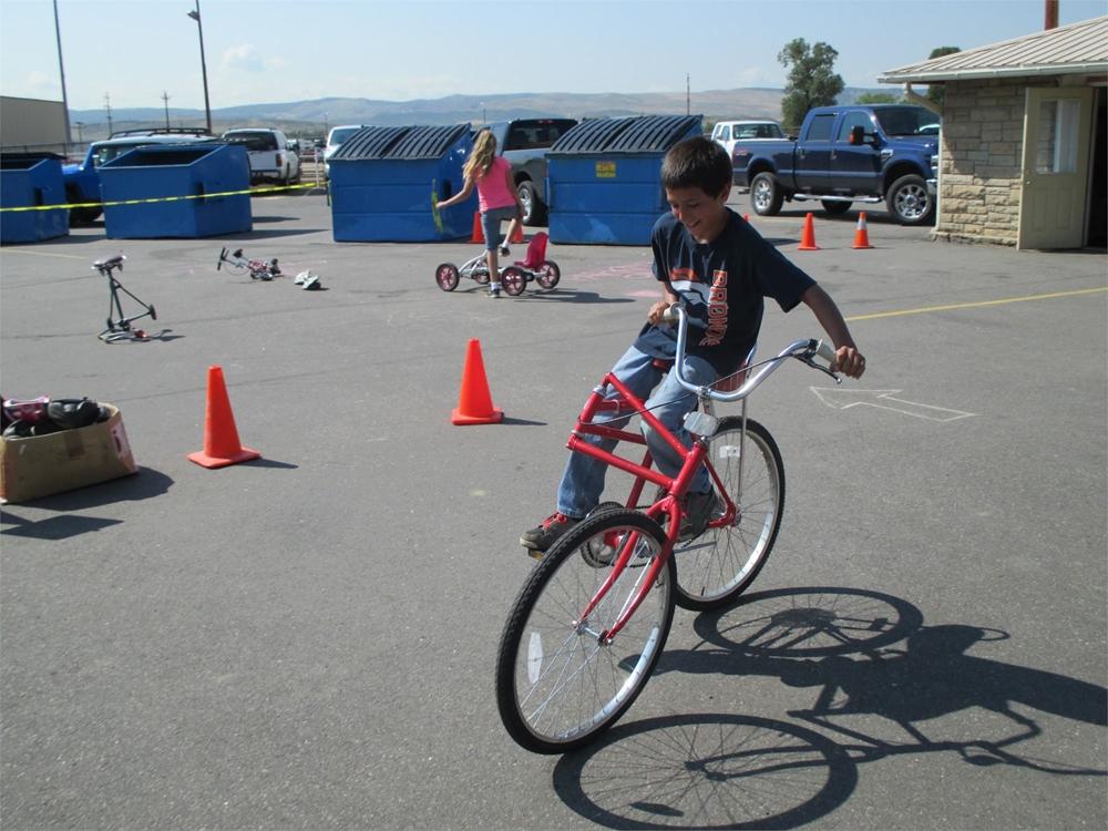 A teenager riding a bike through cones