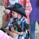 A small cowboy hugging his sheep
