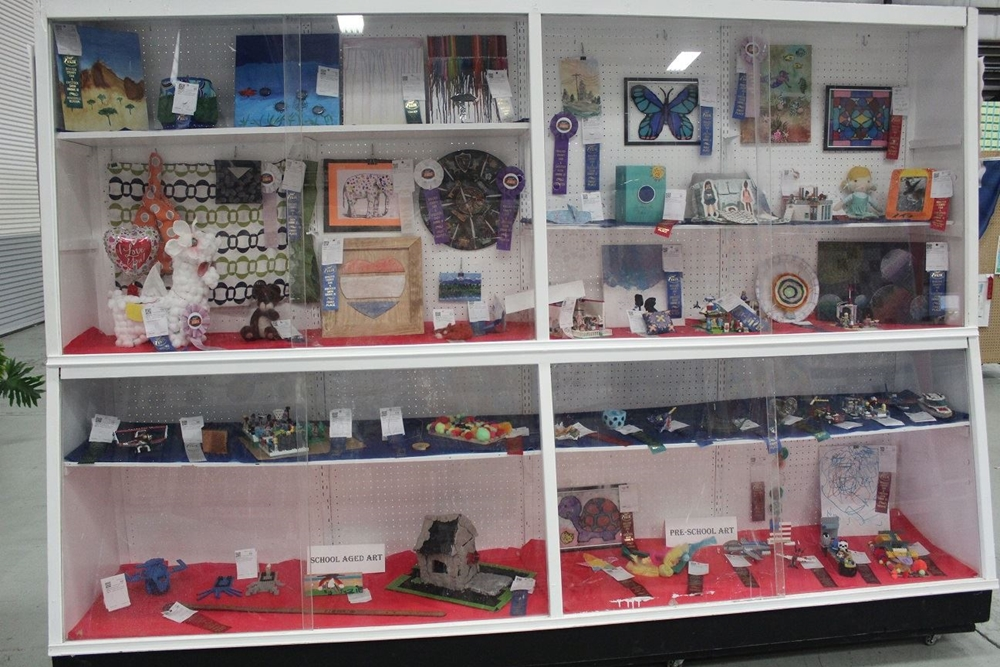 School Aged Art entries displayed in cabinet with ribbons
