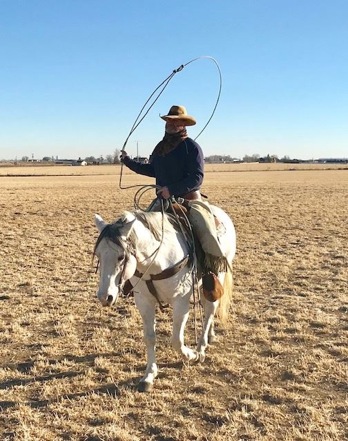 Pastor David Shumpert roping on a white horse