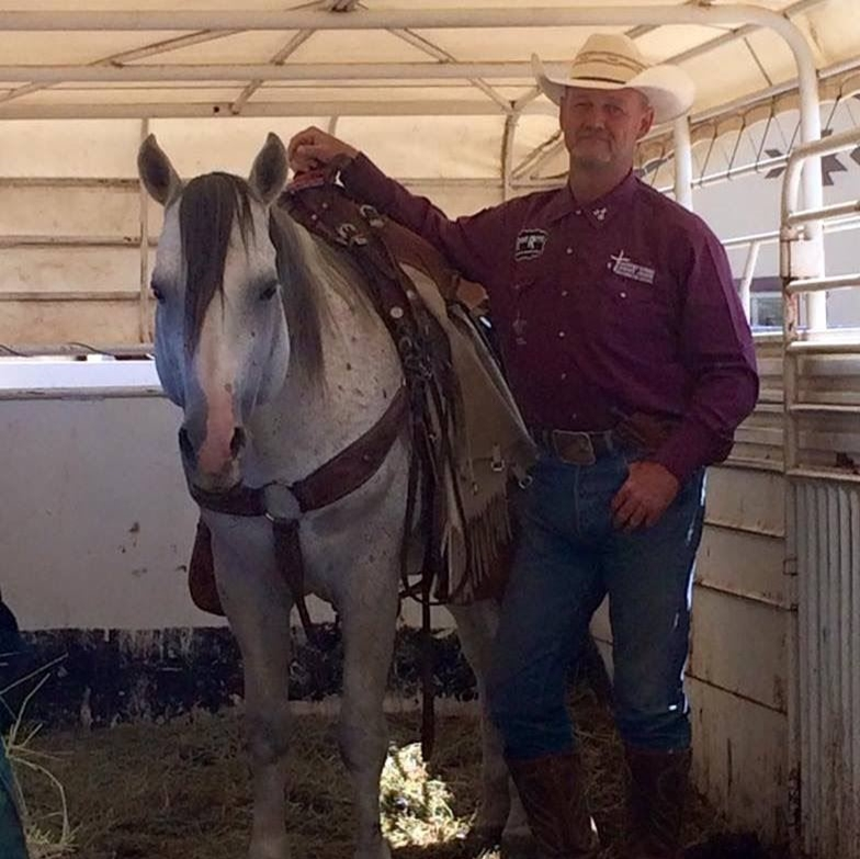 Pastor David Shumpert in a red shirt standing beside his horse