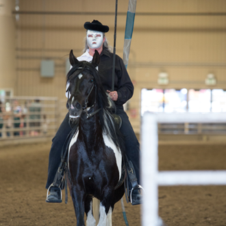 Girl with a mask performing on horseback for audience