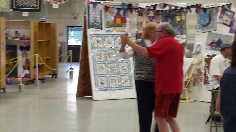 A couple dancing in Exhibit Building on Senior Day