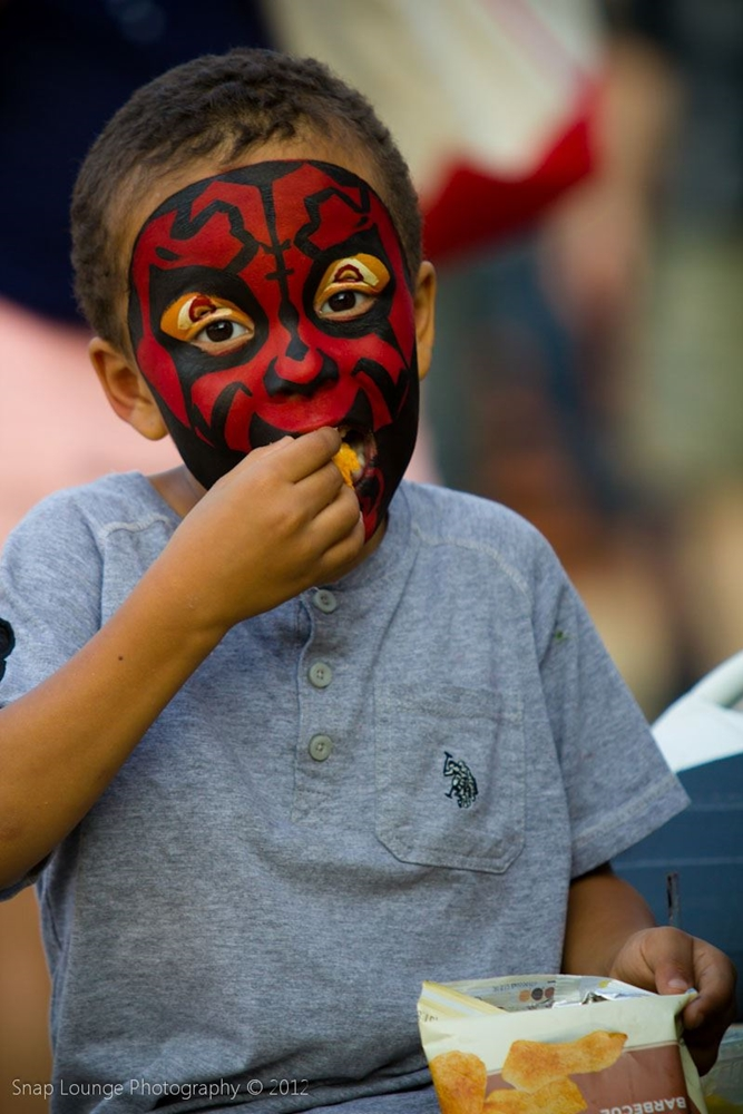 Child with a red face from face painting artist