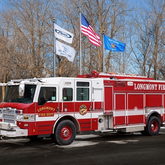 Longmont Red Firetruck with flags blowing in background