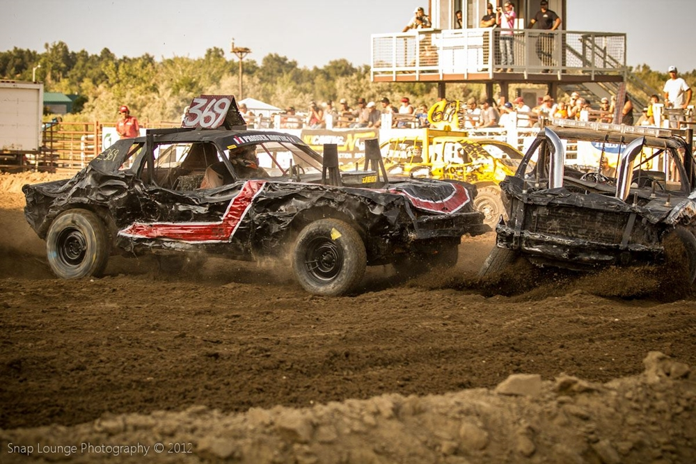 Black Demo Derby car 369 crashing into another car in front of grandstands