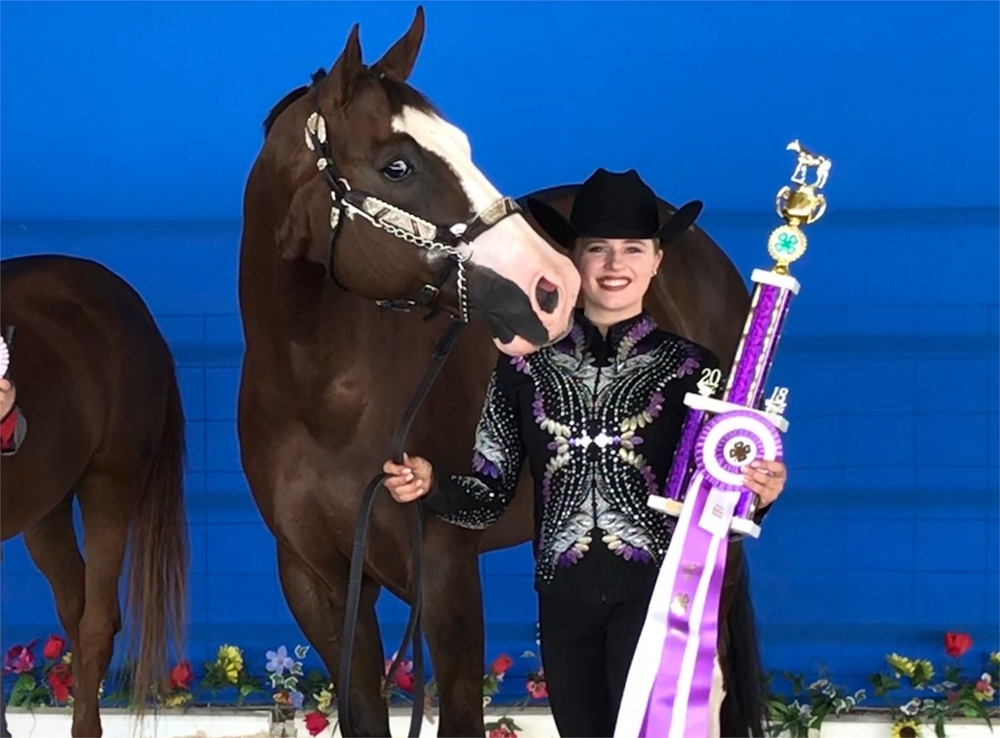 4-H girl beside her horse holding a Grand Champion trophy