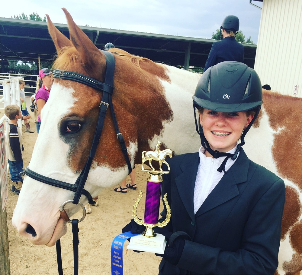 A 4-H girl standing next to her horse holding a trophy smiling