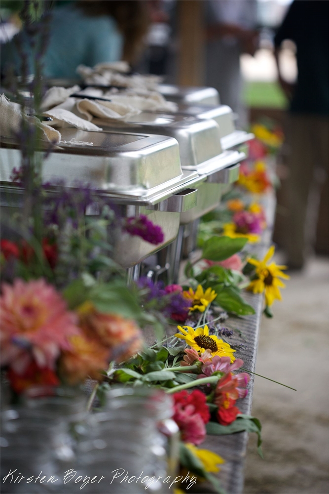The Farm to Table buffet on a table surrounded by fresh flowers and hot dishes