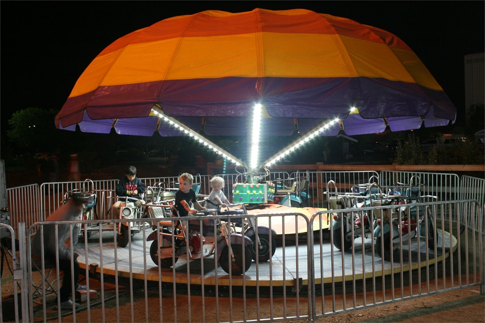 Kids car ride in the carnival area of the fair