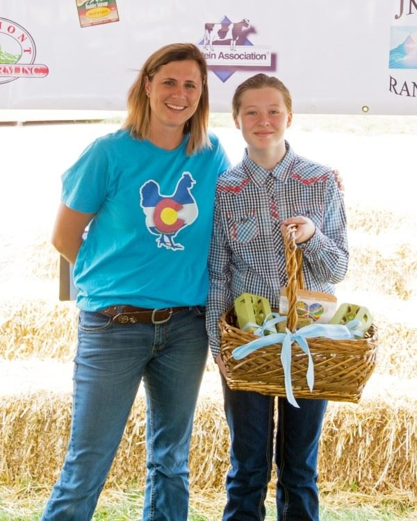 A young girl is holding her filled basket for the 4-H Product Sale