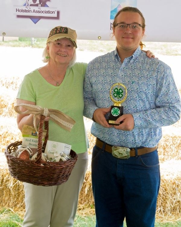 A 4-H boy holding his basket and the trophy he won at the 4-H Product Sale