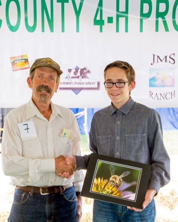 A man shaking a boy's hand while he holds a prize winning photo