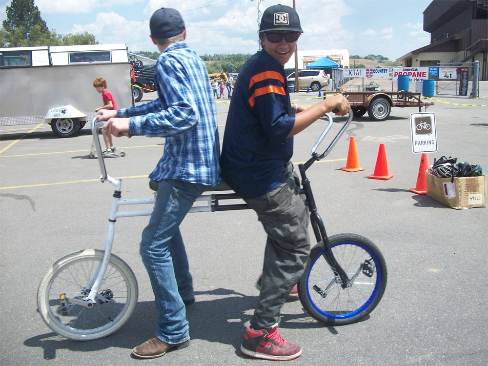 Two guys riding on a backwards tandem bicycle