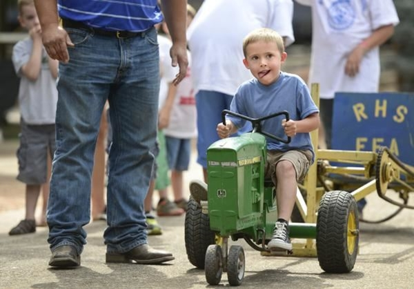 Small child in a pedal pull tractor with an adult looking on