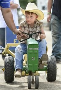 small child in a pedal pull tractor