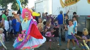 Pippi the Clown strolling the grounds with people watching