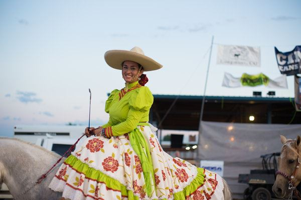Escaramuza charra - a female equestrian side-saddle rider and wearing traditional Mexican costumes that include sombreros, dresses, and matching accessories.