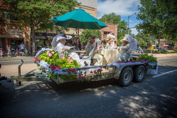 Women dressed in antique white gowns on the back of a trailer waving in the Fair Parade