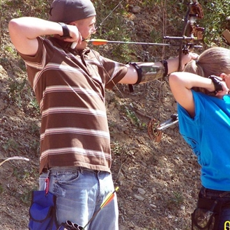 A 4-H youth target practicing with a bow and arrow