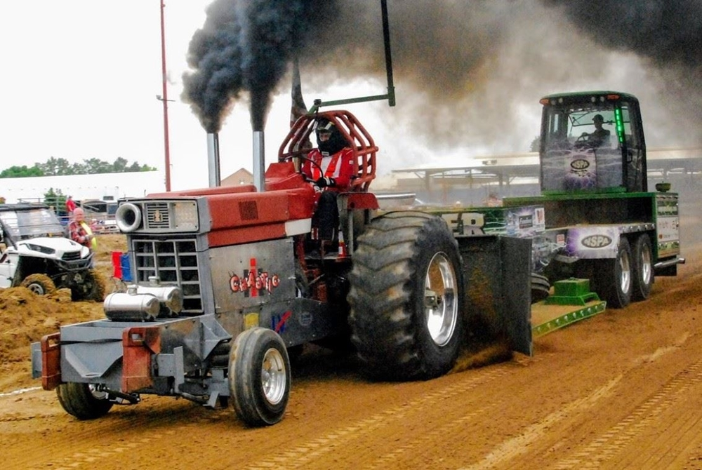 Large red tractor pulling a large green tractor