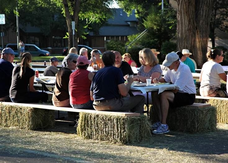 People sitting on hay bales eating the Chuck Wagon breakfast