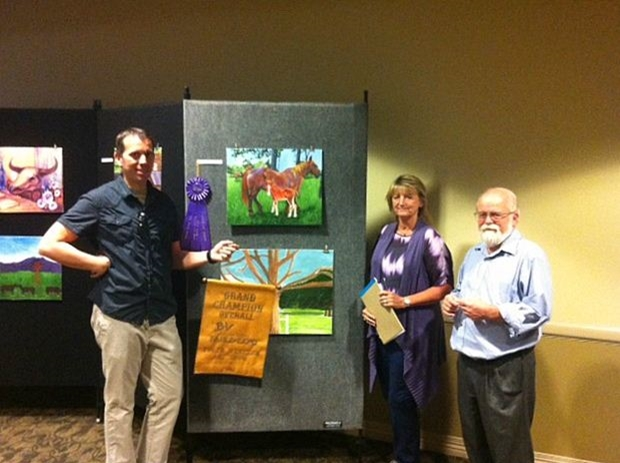 Judges Igor Kraguljac, Coleen Bradfield, and Wayne Smith with the Grand Champion Overall painting by College Station ISD student Brooke Stickland.