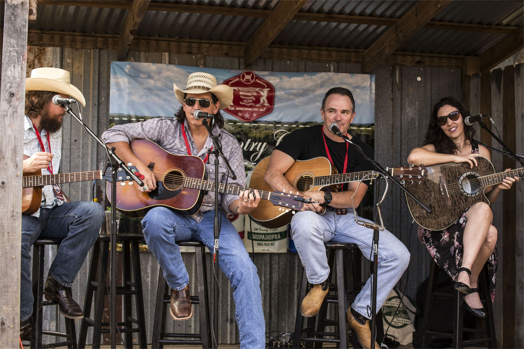 Four different songwriters playing guitars on an outdoor stage.