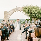 A man and woman getting married outdoors beneath a stone arch. A dog is in the aisle and being petted by a wedding guest