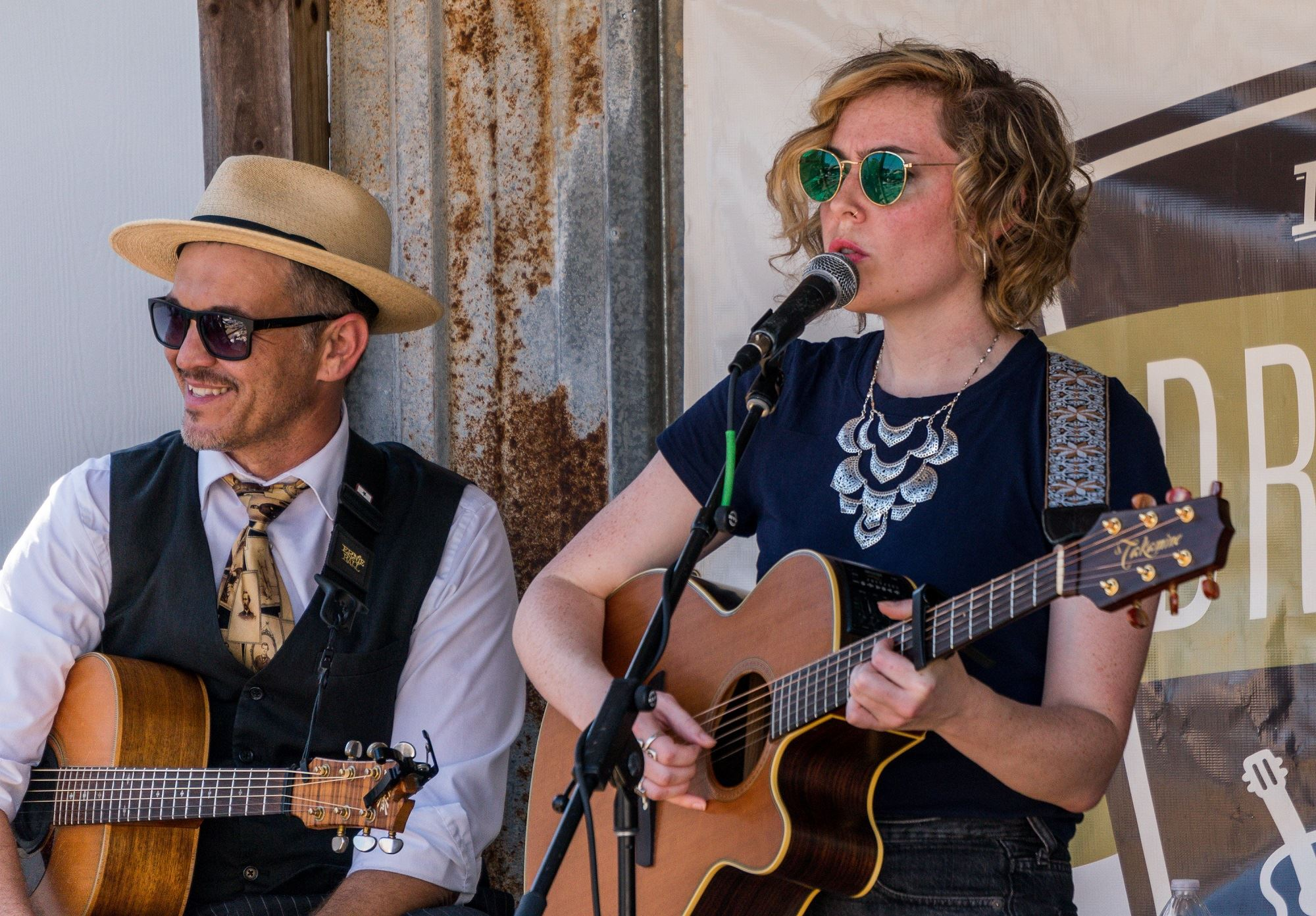 Two songwriters on an outdoor stage.