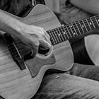 a hand strumming a guitar