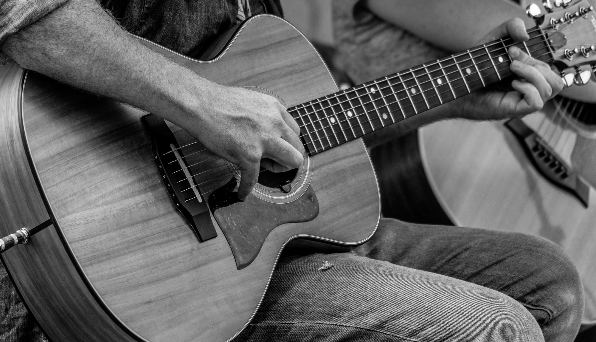 A black and white image of a hand strumming a guitar.
